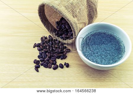 Sweet basil in white cup and coffee beans in sack sisal on wooden background.