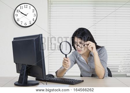 Female worker observes a computer with a magnifying glass in the office