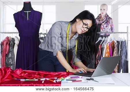 Beautiful female fashion designer working on the table with a laptop computer and clothes hanger on the background