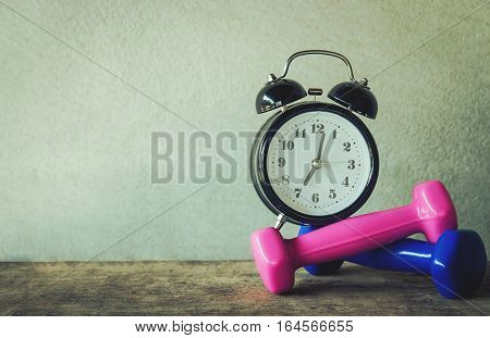 Alarm clock with colorful dumbbell in vintage tone, time to exercise work out concept