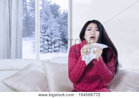 Portrait of young woman sneezing on the sofa while holding a tissue in her hands with winter background on the window