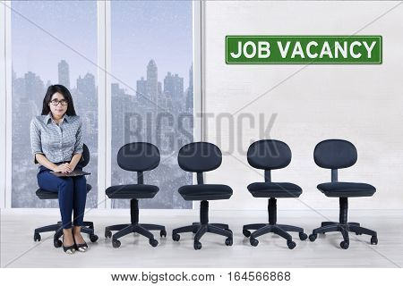 Portrait of attractive woman holding a clipboard and sitting on a chair with empty chairs and text of job vacancy on a board in the office