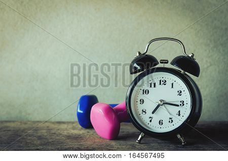 Dumbbells, clock  in vintage tone, health care lost weigh concept