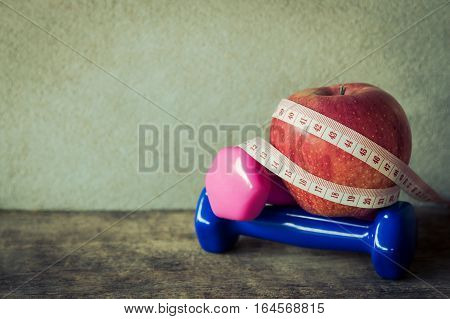 Dumbbells, clock and measuring tape in vintage tone, health care lost weigh concept