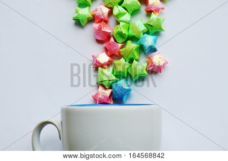 colorful star paper fling from coffee cup on white background