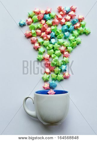 colorful star paper splashing from coffee cup on white background