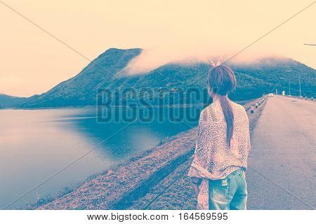 Young Asian girl looking beatiful view of mountains and lake. Retro vintage filter effect.
