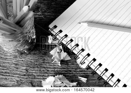 A top view image of an open notebook and several sharpened pencils.
