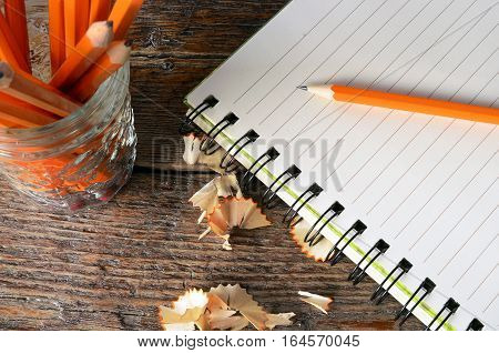 A top view image of an open notebook and several sharpened wooden pencils.