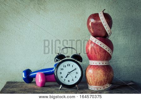 Apple with dumbbells, clock and measuring tape in vintage tone, health care lost weigh concept