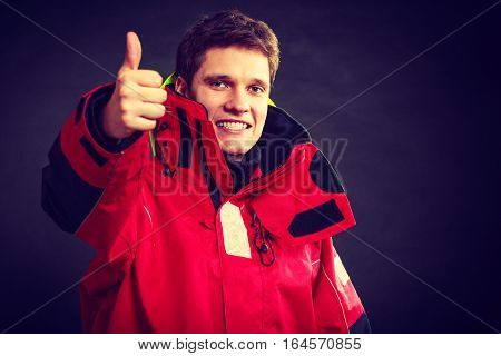 Cheerful man with weatherproof gear. Young male making thumbs up gesture. Adventure outdoors concept.