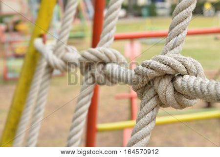 Close-up of rope knot line tied together with playground background,as a symbol for trust, teamwork or collaboration