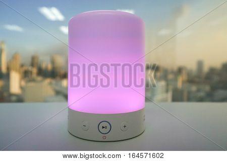 glow smart wireless speaker light in purple on table
