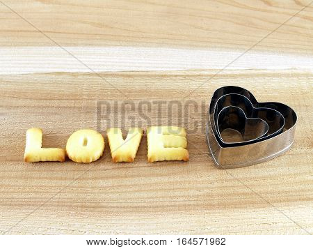 love word, biscuit cookies letters with heart shaped cookie cutter on wooden table background, snack for valentine's day