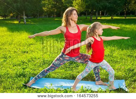 Mother And Her Daughter Outdoors Doing Yoga