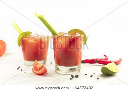 Bloody Mary cocktails with red hot chili peppers, slices of lime, celery sticks, a piece of tomato and copyspace