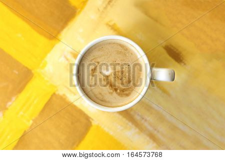 A cup of coffee with milk in a white cup on on a golden texture with a place for text