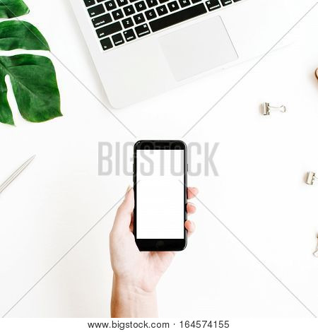 Mockup of smartphone with blank copy space screen in female hand. Flat lay top view workspace