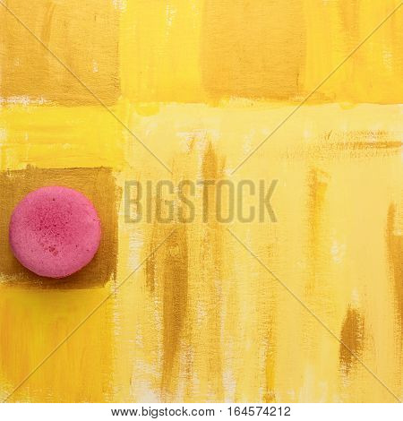 A photo of a vibrant macaron, shot from above on a bright yellow background texture, with copyspace