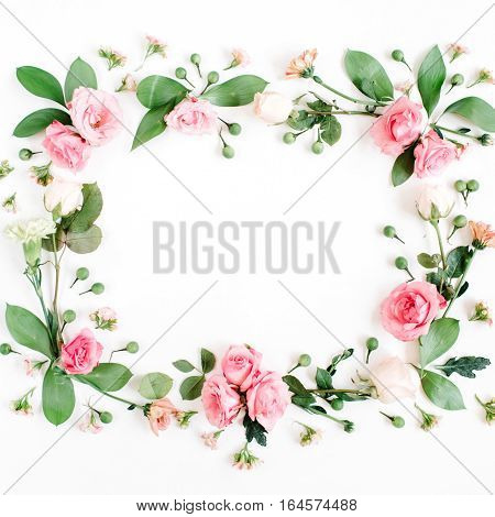 Round frame made of pink and beige roses green leaves branches on white background. Flat lay top view. Valentine's background