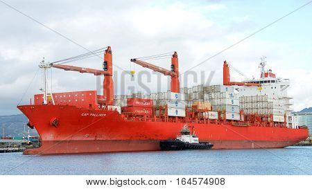 Oakland CA - December 02 2017: Tugboat PATRICIA ANN on the port side of cargo ship CAP PALLISER maneuver out of the Port of Oakland.