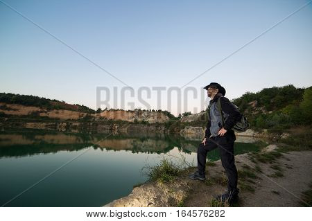 Hiker man with backpack standing next to a mountain lake at dawn.