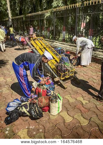 MUMBAI, INDIA - NOVEMBER 10, 2016: In Mumbai, a well-known logistics system delivers lunches through the streets. Here one dabbawala or lunchbox delivery person is transferring lunch bags and boxes to the cart for delivery.
