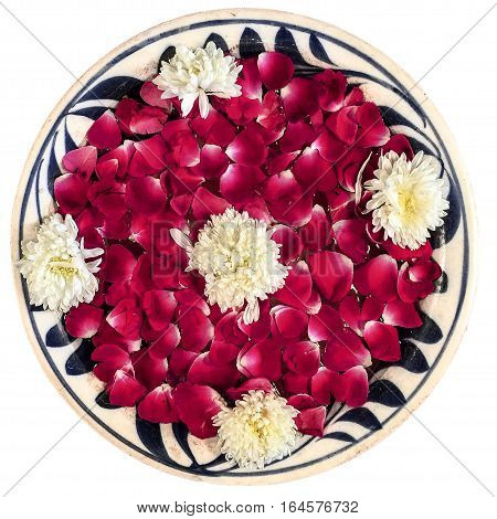 A bowl of water filled with rose petals and other flowers forms a ornamental floral arrangement. Isloated to a white background.