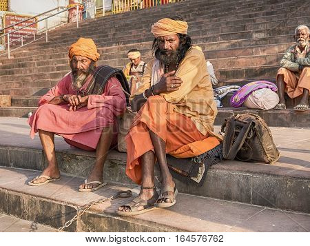 RISHIKESH, INDIA - NOVEMBER 16, 2016: Two sadhus or holy men sit in colorful attire the steps of a ghat near the Ganges River in the holiy city of Rishikesh, India.