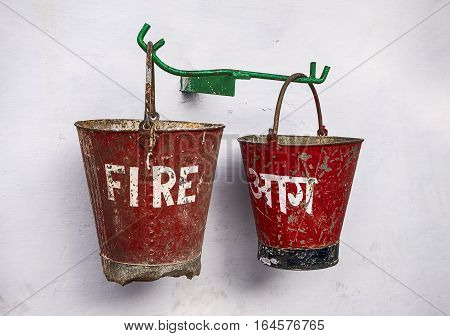Two fire buckets with red paiint are offered as safety equipment on a street in Rishikesh India.