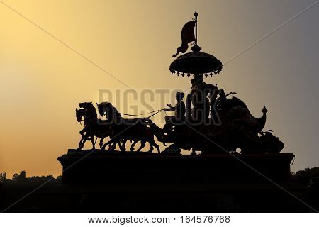 An ornamental statute of people riding a carrage is silhouetted against the evening sunlight in Rishikesh India.