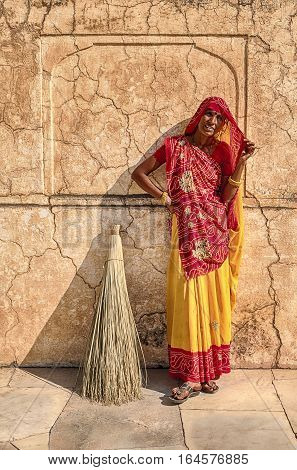 AMER, INDIA - NOVEMBER 18, 2016: An anonymous woman with a traditional broom stands against a wall in the Amber Fort in the city of Amer near Jaipur, India.