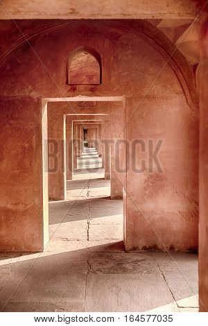 A long passageway of red sandstone arches alternate light and shadow details near the entrance to the Taj Mahal in Agra India