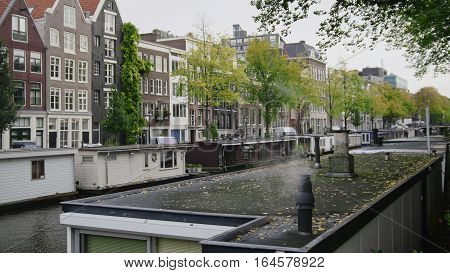 Smoke from houseboats along canals, Amsterdam, Netherlands, wide angle