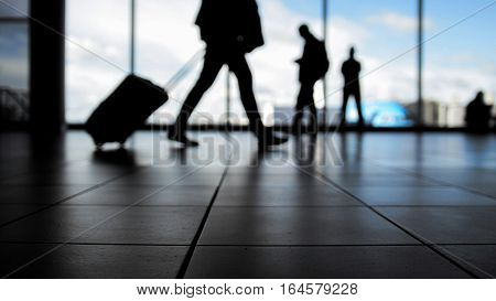 Travellers in airport walking to departures by escalator in front of window, silhouette, blue colors