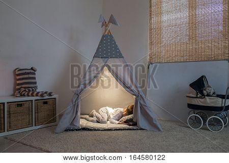 The boy sleeps in the teepee playroom in the lamplight.