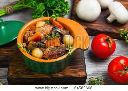 Stew meat in Burgundy in green ceramic pot with carrots onions. Spices for meat Burgundy thyme cherry tomatoes mushrooms champignons. Light white wooden background.