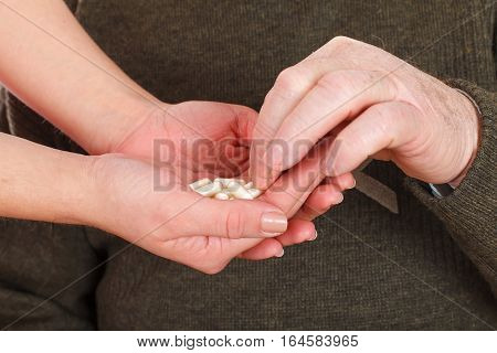 Close up picture of a senior man receiving his pills from his caregiver