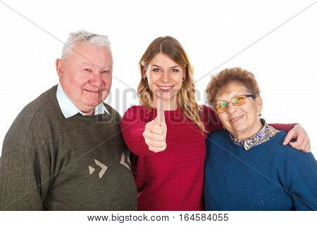 Picture of an elderly couple with their young caregiver showing thumbs up