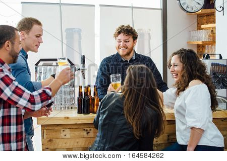 company of two women and three men drinking craft beer together