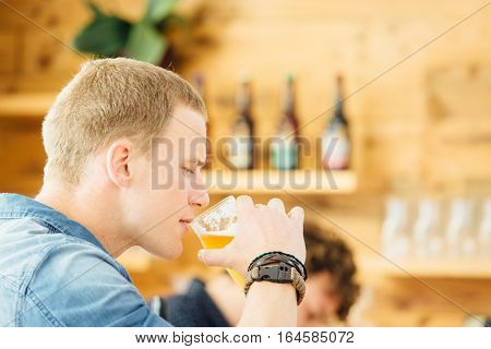 Side view of handsome blond man drinking craft beer. Bokeh