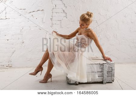 Beautiful sexy blonde woman in white dress posing against white wall