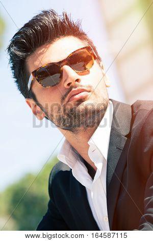 Gorgeous stylish man with sunglasses. Stubble and blacks hair. Intense light. White shirt and stylish jacket.