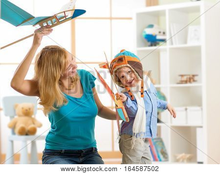 Mother and her child son having a fun playing with toy airplanes at home