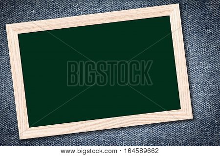 Chalkboard or Empty bulletin board with a wooden frame on denim jeans background with copy space for text or image.