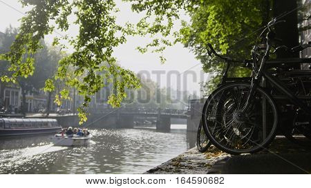 View of wheel of bicycle on the Amsterdam amstel canal, next to floats tour boat, sunny european autumn, Netherlands