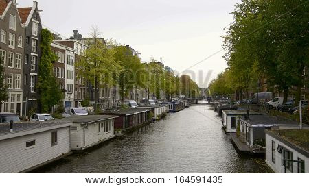 Vessels and houseboats along canals, Amsterdam, Netherlands, wide angle