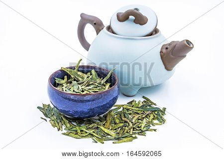 Green tea Longjing (Dragon Well tea) - Chinese green tea with small clay pot isolated on white.