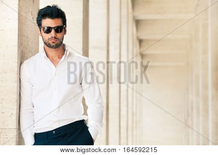 Charming and fashionable young man with sunglasses. Outdoors leaning against the marble wall.