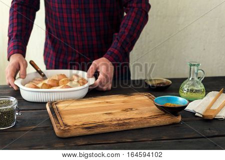 Wooden cutting board with place for product on a wooden kitchen table in the background male preparing chicken leg
